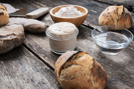 Still life setting of sourdough starter yeast and bread ingredients on rustic wooden boards.