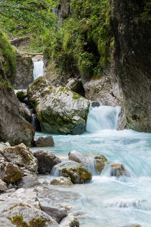 Long exposure image of a beautiful mountain stream flowing through rocks and stones in a valley.