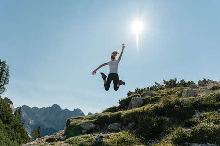 View from behind of a young female hiker jumping up high enjoying life and the beautiful view of mountains under clear sunny sky. Imagens