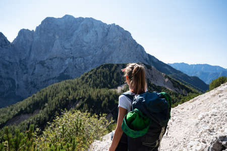 View from behind of a young female hiker with a backpack stopping to look at the beautiful view of mountains.