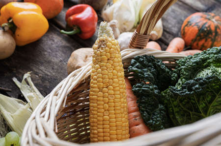Variety of fresh autumn vegetables in a wicker basket.