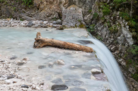 Part of tree trunk lying in beautiful stream just above the waterfall in a long exposure image.