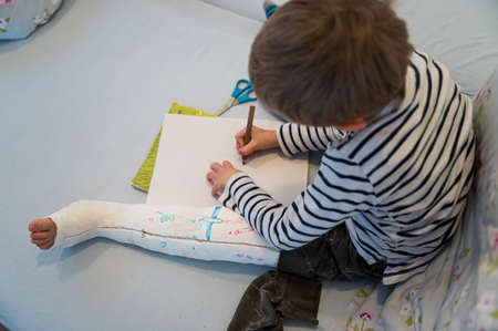 Aerial view of toddler boy with his leg in a cast drawing on white piece of paper.