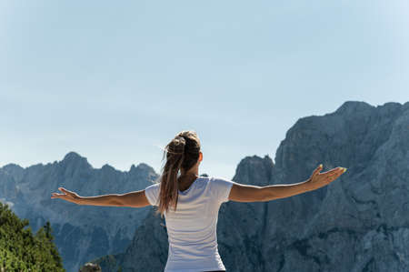View from behind of a young female hiker enjoying life standing with arms wide open enjoying the view of the Alps. Imagens