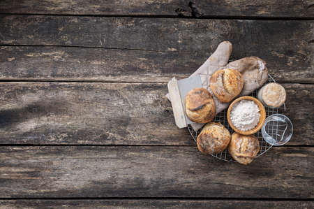 Top view of freshly baked sourdough bread buns, water, flour and starter yeast placed on a round cooling rake over rustic wooden boards. Imagens