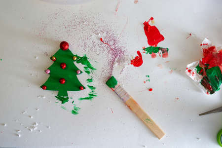 Top view of a paintbrush on a working surface next to a handmade and colored wooden christmas tree ornament.