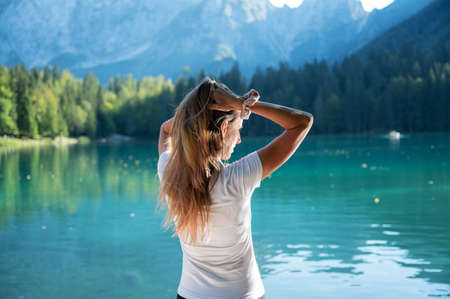 Young woman lit by the sun enjoying herself by the beautiful lake Fusine in Italy. Imagens
