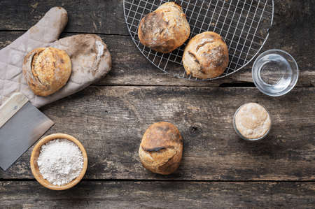 Top view of home made freshly baked sourdough bread buns, starter yeast, water and flour on rustic wooden boards.