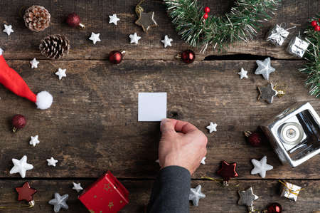 Top view of male hand placing a small blank piece of paper in the center of holiday setting full of christmas ornaments. Imagens