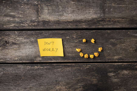 Dont worry message on a yellow post it paper with a smiling face made of tiny wrinkled papers. Over rustic wooden backgrounds.