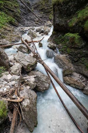 Long exposure image of tree logs lying in beautiful stream of water running through rocks and stone. Imagens