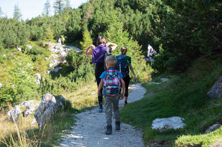View from behind of adults and children hiking, walking on a mountain trail with backpacks.