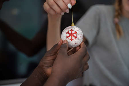 Hand of a child holding white and red shiny holiday christmas bauble. Imagens