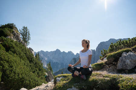 Zen young woman sitting in lotus position meditating on a mossy rock in beautiful nature high up in the mountains.