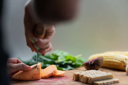Low angle view of a woman cutting sweet potato on a cutting board full of vegetables and tempeh protein.