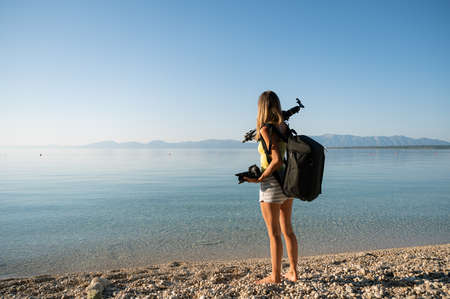 Young female photographer with tripod on her shoulder, camera in her hand and photographic backpack on her back standing on beautiful pebble beach by calm morning sea.