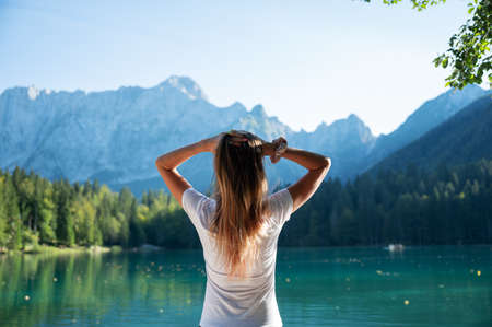 View from behind of a young woman standing by the beautiful lake Fusine, Italy, going with her hands through her long hair. Lit by beautiful sun flare. Imagens