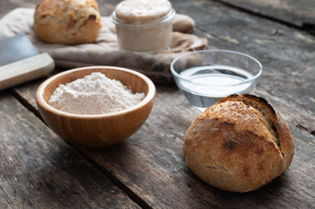 Still life of home made sourdough bread, flour, water and starter yeast. Imagens
