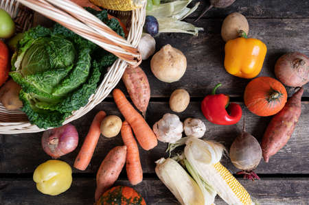 Top view of various autumn vegetables in a wicker basket and around it placed on rustic wooden desk.