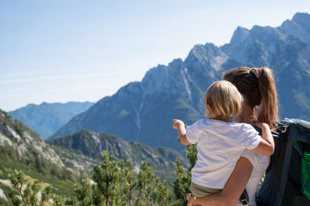 Young mother holding her toddler daughter  looking at beautiful view of mountains as they hike together on a sunny day.