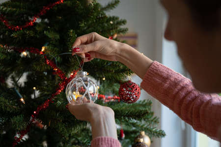 Woman with red holiday manicure hanging transparent shiny bauble on a christmas tree at home.