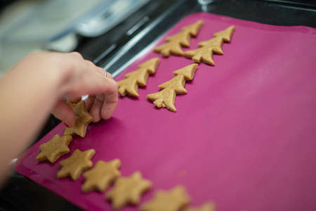 Closeup view of female hand placing winter holiday shaped cookies on a baking tray lined with pink silicone.