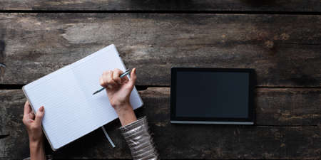 Top view of a woman about to make notes in a blank open notepad next to a digital tablet. Stockfoto