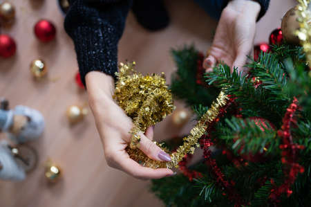 Top view of a woman decorating holiday christmas tree with shiny golden ribbon. Imagens