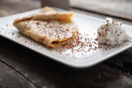Low angle view of homemade vegan crepe filled and folded and served with chocolate sprinkles and whipped cream. Imagens