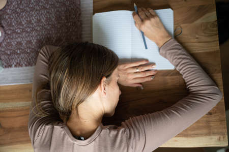 Top view of a young woman who fell asleep on notebook while studying  on wooden desk with pencil in her hand.