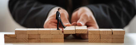 Businessman building a bridge of wooden blocks for his partner to walk across in a conceptual image of teamwork and cooperation.