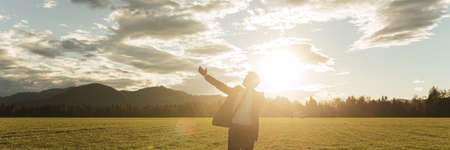 Young businessman standing in beautiful green meadow backlit by the sun under dramatic sky with his arms wide open.