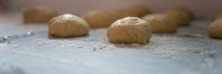 Wide view image of ball shaped pastry dough for bread or donut resting and rising on flour dusted kitchen counter.