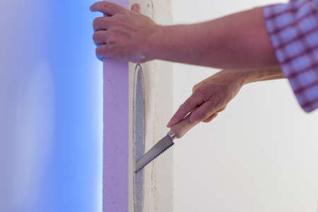 Hand of a worker designing a loop hole in a wall as a decoration element in interior design conceptual image. Standard-Bild
