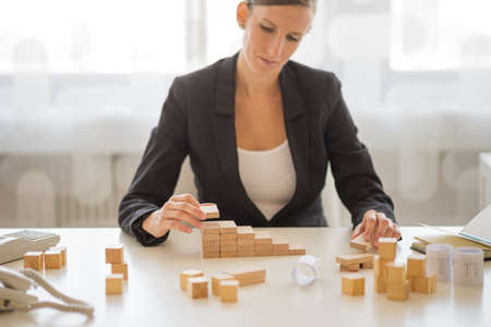 Young businesswoman sitting in a bright office building starway of wooden pegs in a conceptual image of vision and startup.