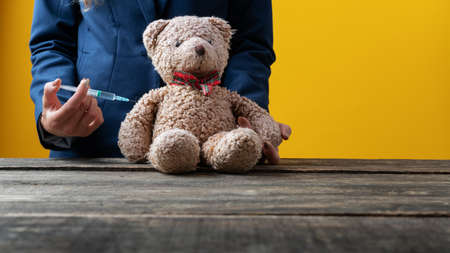 Closeup of a medical doctor vaccinating a teddy bear toy in a conceptual image. Standard-Bild