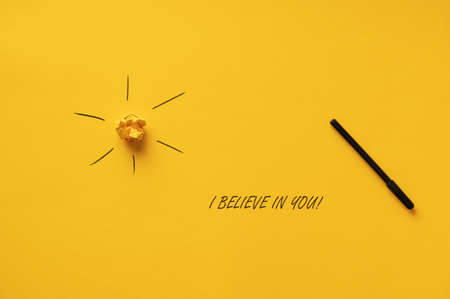 I believe in you sign spelled with black marker over yellow background next to the sun.