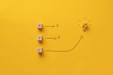 Conceptual image of brainstorming and idea with a light bulb over yellow background.