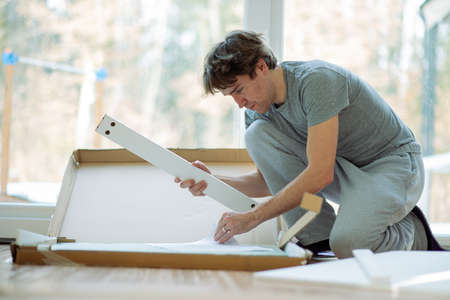 Young man opening a carton furniture box to build the table at home. Standard-Bild