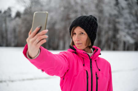 Young woman in pink winter jacket and black hat taking a selfie with her phone standing in beautiful snowy nature.
