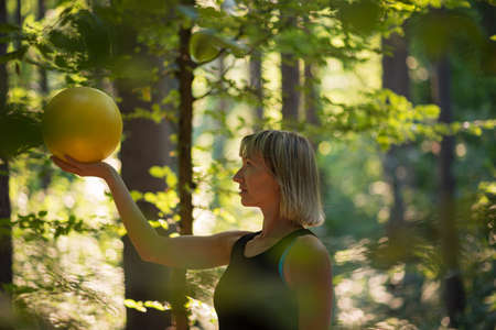 Young woman in sporty clothes standing in a sunlit forest holding yellow pilates ball.