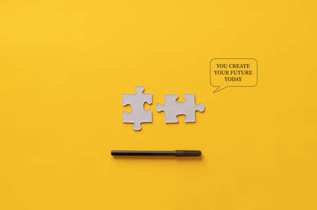 You create your future today message written on yellow background next to two matching puzzle pieces and black marker.