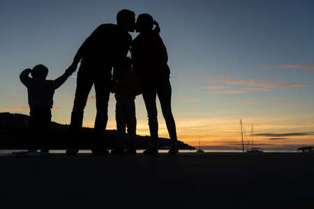 Silhouette of young couple kissing while they stand by the evening sea with their toddles children.