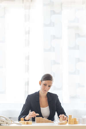 Young businesswoman in her office building steps of wooden pegs in a conceptual image of vision and strategy.