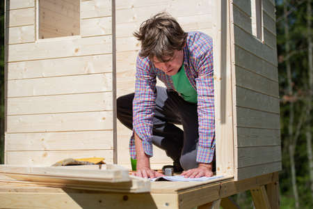 Young man reading instructions as he builds  a wooden playhouse in the backyard.