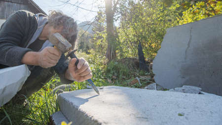 Artist carving in stone with great precision using a mallet and chisel. Standard-Bild