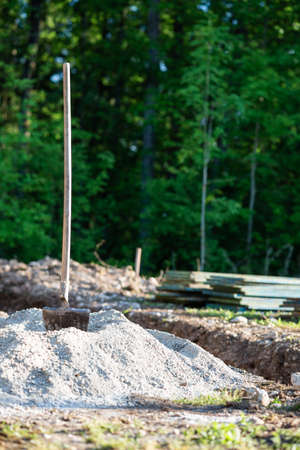 Construction site outdoors with a shovel in a pile of gravel.
