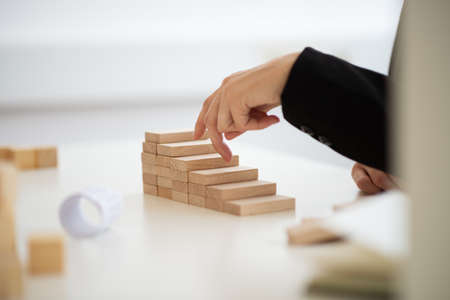 Closeup view of businesswoman walking her fingers up the conceptual steps made of wooden blocks.