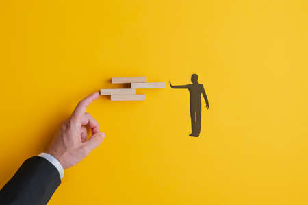 Conceptual image of teamwork and problem solving with male hand and silhouetted male figure arranging wooden blocks. Standard-Bild