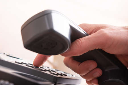 Closeup low angle view of a male and holding black landline telephone receiver dialing a phone number.